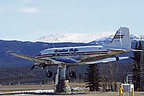 A historic  Canadian Pacific Airlines DC-3 passenger plane is mounted so perfectly on  a pedestal at the Whitehorse International Airport that the slightest breeze causes it to swing around to point into the wind.